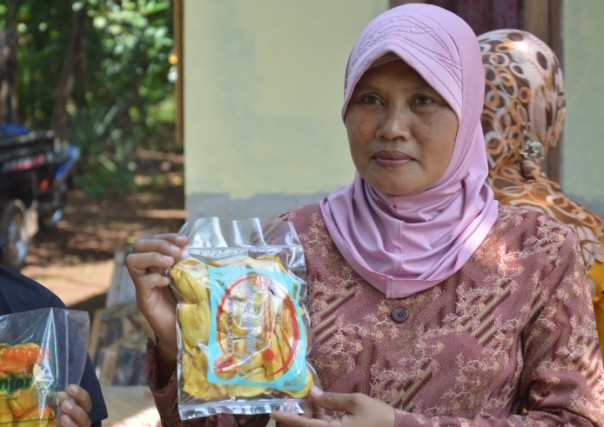 Kaswati stands at her stall in Pagon village, Indonesia, holding a pouch of jackfruit snacks.TRF/Saleem Shaikh