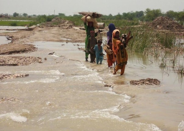 A family carries their belongings as they wade through floodwaters in Dera Allah Yar, in the Jaffarabad district of Pakistan's Balochistan province, Aug. 6, 2013. REUTERS/Amir Hussain